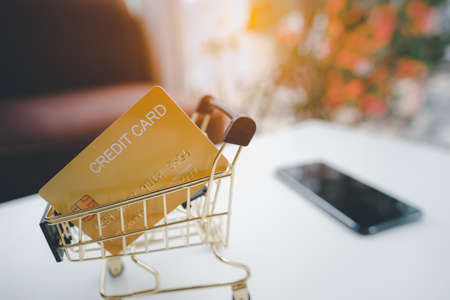 Golden credit card in the Shopping Cart against smartphone on white table. Imagens