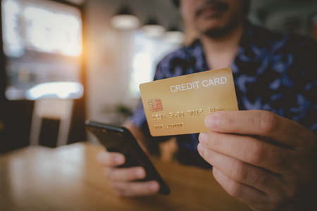 Man are holding credit card and using mobile phone to pay for online shopping in a coffee shop. Online payment Concept.