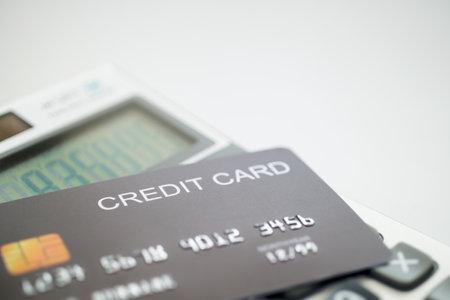 Black credit card on a calculator. Close up. Imagens