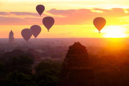 Hot air balloons fly over the ancient pagodas of old Bagan in Myanmar at sunrise. Bagan, Myanmar. Imagens