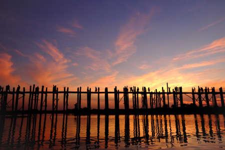 Silhouetted of people on U Bein Bridge at sunset, Amarapura, Mandalay, Myanmar. Imagens