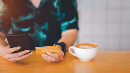 Woman are holding credit card and using mobile phone to pay for online shopping in a coffee shop. Online payment Concept.