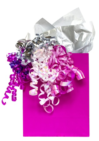 Bright pink gift bag with festive multicolored ribbons and silver paper on white background Stock Photo