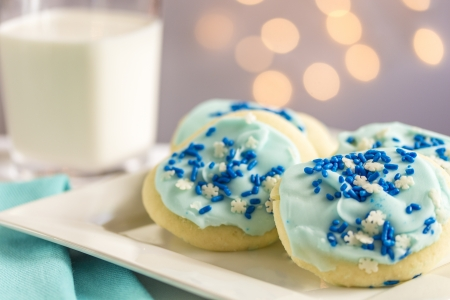 Sugar cookies with blue and white snowflakes and glass of milk with lights photo