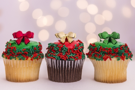 Three vanilla and chocolate christmas cupcakes with green, red and gold bows and lights photo