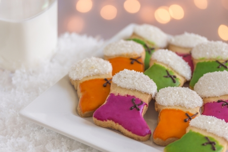 Orange, green and purple stocking cookies with sugar on plate in snow and a glass of milk with lights Stock Photo