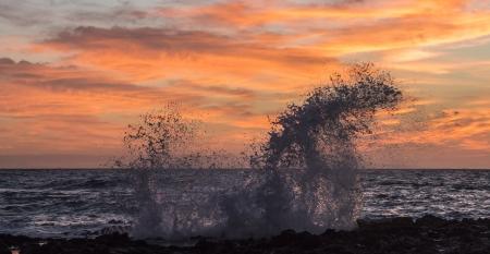Water splashing on rocks at sunrise on the shore of Sandy Beach in Hawaii Stock Photo