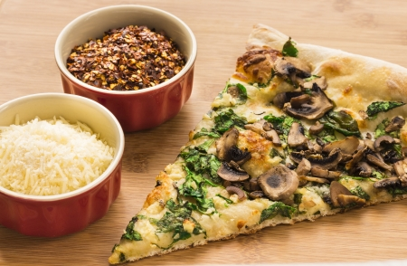 Slice of spinach, mushroom, garlic pizza on a bamboo board with grated parmesan and red pepper flakes Stock Photo - 17032342