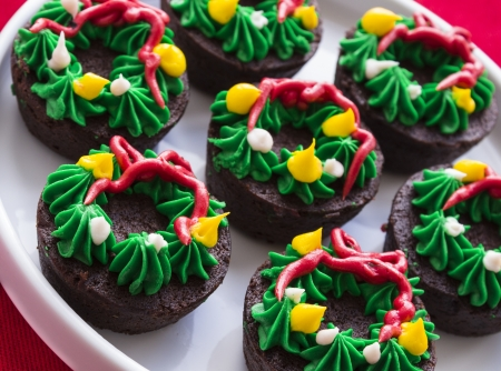 Group of brownies with wreath icing decoration on red tablecloth