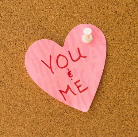 You & Me written on pink heart memo with pattern attached to cork board with white push pin photo