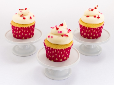 xoxo: Vanilla cupcakes with white frosting and xoxo sprinkles on pedestals