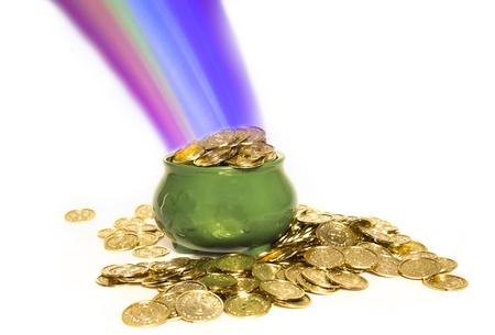the end of a rainbow: Una olla verde con los tr�boles llenas de monedas de oro al final del arco iris aislado en blanco