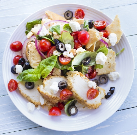 Salad with pita bread, cherry tomatoes, basil, red onion and kalamata olives served with breaded chicken and feta cheese Stock Photo - 18287388