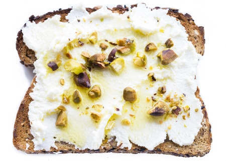 Ricotta spread on rustic toast, drizzled with olive oil and sprinkled with crushed pistachios Stock Photo