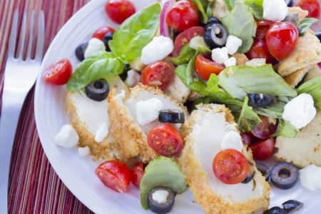 Salad with pita bread, cherry tomatoes, basil, red onion and kalamata olives served with breaded chicken and feta cheese Stock Photo - 18287399