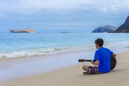 Young man playing guitar on beautiful Waimanalo Beach in Oahu, Hawaii