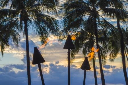 Lit tiki torches at sunset in Waikiki, Oahu, Hawaii