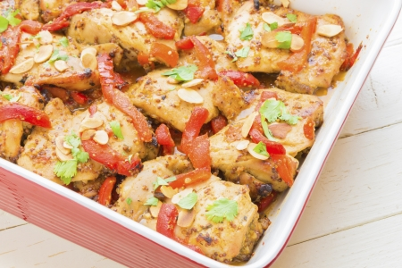 Baked honey mustard chicken thighs with roasted red bell peppers, toasted almonds and parsley