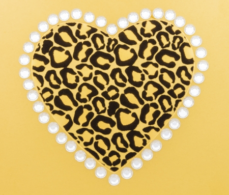 Black and gold animal print heart surrounded by white rhinestones on gold background