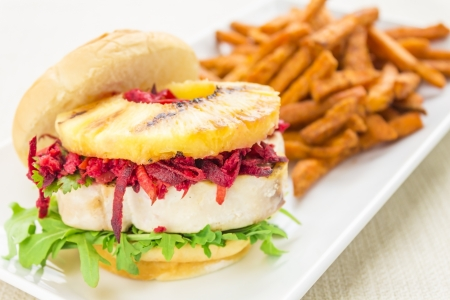 Grilled ahi tuna on arugula, topped with carrot, beet, jicama slaw and grilled pineapple on sweet Hawaiian bread bun photo