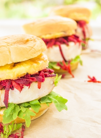 ahi: Grilled ahi tuna on arugula, topped with carrot, beet, jicama slaw and grilled pineapple on sweet Hawaiian bread bun Stock Photo
