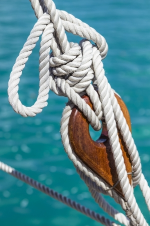 A wooden deadeye with rope on a sailing vessel Archivio Fotografico