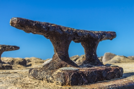 cleat: A large old rusty boat dock cleat