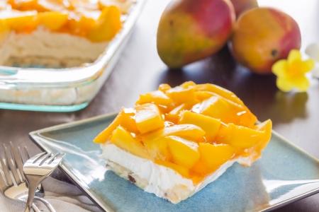 decadent: Decadent cheesecake topped with fresh mango and orange jello with macadamia nut crust Stock Photo