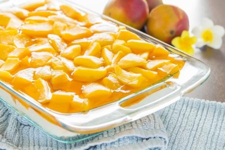 Decadent cheesecake topped with fresh mango and orange jello with macadamia nut crust Stock Photo