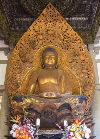 Amida, a carving of Buddha eighteen feet tall and covered in gold leaf at the Byodo-In Temple in the Valley of the Temples on Oahu, Hawaii