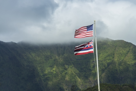The Hawaiian and American flags flying high together in front of the Koolau Mountains on Oahu, Hawaii