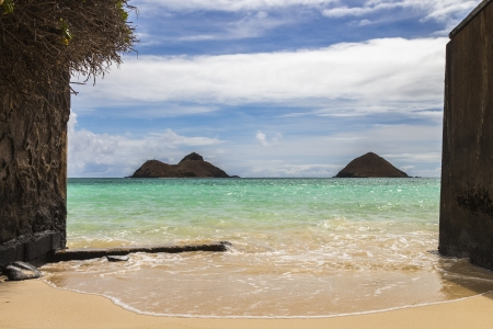 A narrow beach opening with a view of Na Mokulua Islands, also known as The Mokes and Twin Islands, in Lanikai on Oahu, Hawaii Stock Photo