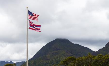 hawaii flag: The Hawaiian and American flags flying high in front of the Koolau Mountains on Oahu, Hawaii Stock Photo