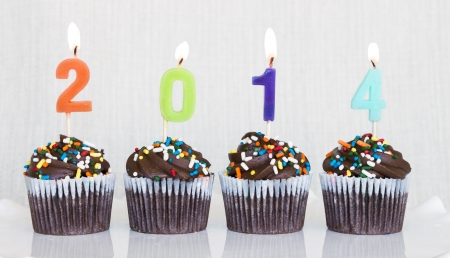 Lit multicolored candles that spell 2014 in chocolate mini cupcakes with colored sprinkles Stock Photo