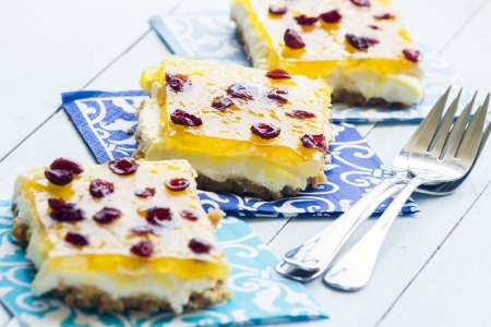 Hawaiian pineapple bars made with a graham cracker crust, cream cheese and marshmallow filling, jello and crushed pineapple topping, and sprinkled with dried cranberries