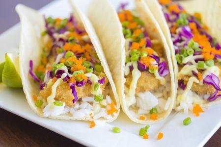 Fried breaded ahi tuna, rice, purple cabbage, green onions, masago (capelin fish roe) and wasabi mayonnaise on corn tortillas Stock Photo