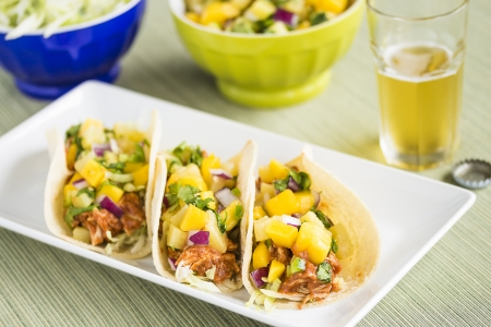 Corn tortillas filled with shredded lettuce, shredded barbecue chicken and topped with mango pineapple salsa photo