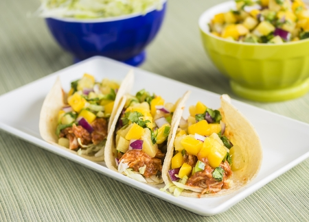 Corn tortillas filled with shredded lettuce, shredded barbecue chicken and topped with mango pineapple salsa Stock Photo