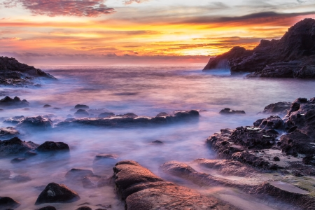 Intensely colorful sunrise at Halona Cove, commonly known as Eternity Beach, on Oahu, Hawaii Stock Photo