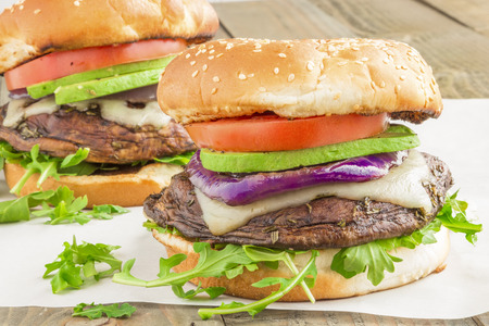 Portobello burgers on a bed of arugula, topped with melted swiss cheese, grilled purple onion, avocado and tomato Stock Photo