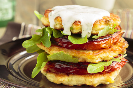 Corn fritters stacked with roasted tomatoes and arugula, served with ranch dressing Stock Photo
