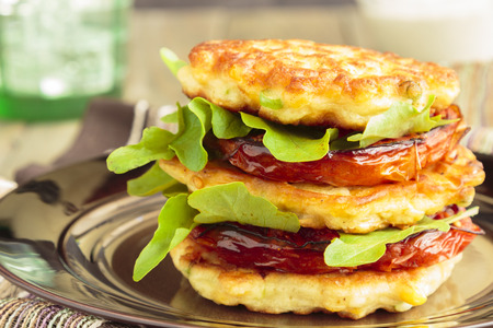 Corn fritters stacked with roasted tomatoes and arugula