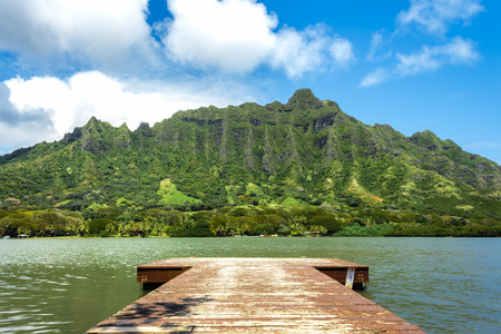 A pier on Molii Fishpond looking toward the Koolau Mountain Range at Kualoa Ranch on Oahu, Hawaii