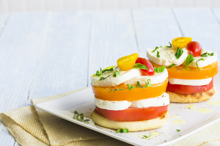 An english muffin stacked with a caprese salad made of tomato and mozzarella cheese
