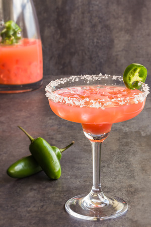 Spicy Hawaiian margarita made by soaking sliced jalapenos in  guava juice, tequila and grand marnier, with pink Hawaiian sea salt
