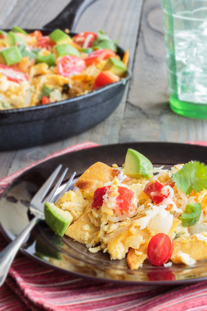Tex-Mex breakfast migas made of eggs scrambled with onions, red bell pepper, jalapeno, cheese, topped with cherry tomatoes, avocado and cilantro