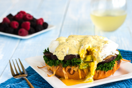 Vegetarian eggs benedict made with gouda cheese, steamed kale, sauteed portobello mushroom. poached egg and thyme sabayon sauce on a kaiser roll, served with red and black raspberries and white wine