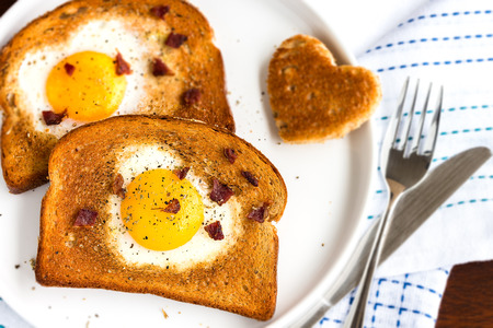 bacon love: Egg fried in a heart-shaped toast cutout sprinkled with bacon crumbs, cracked pepper and thyme Stock Photo