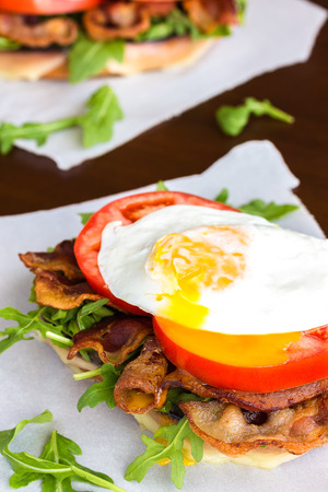 Open-faced BLT sandwich with provolone cheese, arugula, bacon, tomato and a fried egg on sweet potato bread