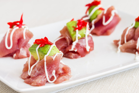 Carpaccio of Ahi tuna topped with avocado and pickled ginger, drizzled with aioli